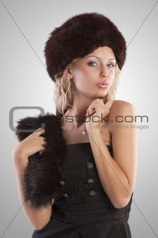 blond girl with fur hat on spotlight background