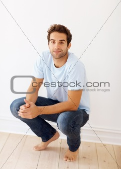 Handsome man in casual clothes squatting
