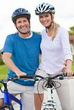 Happy Man &amp; Woman Couple Riding Bikes
