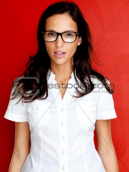 Pretty young lady in glasses against red background