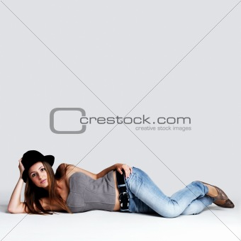 Trendy young woman lying on floor with lots of copyspace