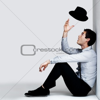 young man sitting on floor and playing with hat