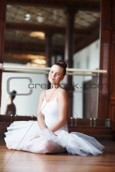 Young beautiful ballet dancer resting on wooden floor