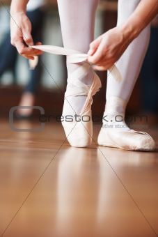 Ballerina putting her shoes on with a blurred man in background