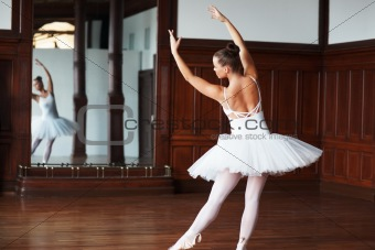 Ballerina wearing white tutu dancing in front of a mirror