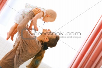 Young mama playing with baby by rising her up