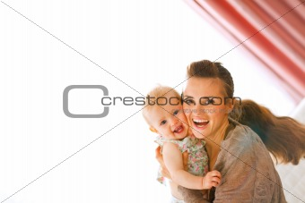 Portrait of happy young mother with her smiling baby