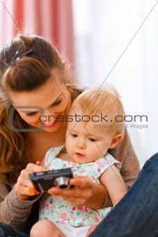 Young mother showing interested baby photos in camera
