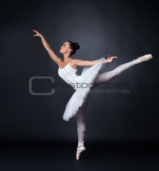 Young ballerina dancing gracefully against black background