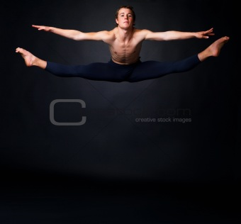 Young ballet man jumping against black background - copyspace