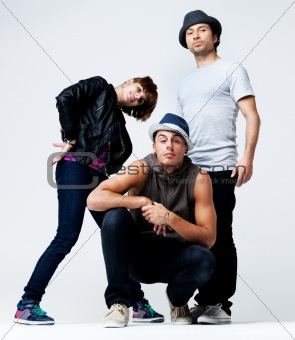 Team of break dancers posing together on grey background