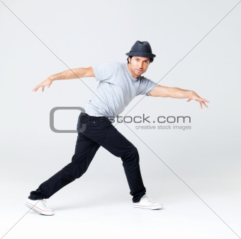 Young male hip hop dancer posing on grey background  