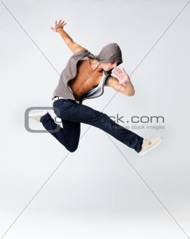 Young male breakdancer jumping in air