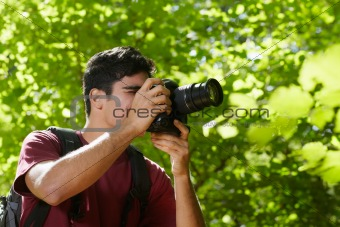 young male photographer hiking in forest