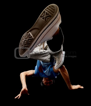 Funky young male hip hop dancer performing head spin