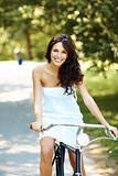 Gorgeous young girl with her cycle in park
