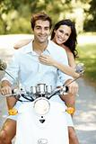 Young couple riding on moped in a park