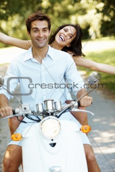 Happy love couple in a park on scooter enjoying themselves