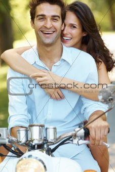 Happy young love couple on a scooter in a park