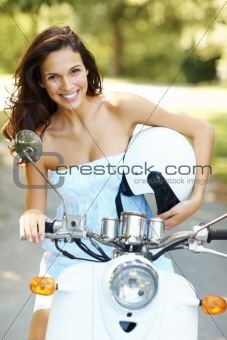 Smiling girl on scooter holding a helmet