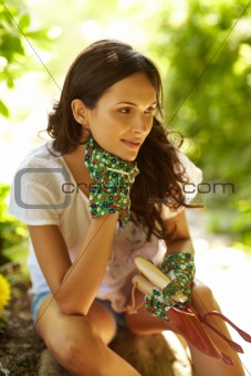 Thoughtful young woman with gardening tools outdoor
