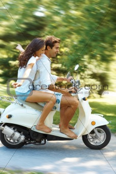 Young love couple enjoying ridding on scooter