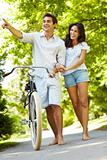 Happy young couple with bicycle in forest looking away