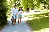 Happy couple walking with bicycle in a park