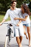 Romantic couple with a cycle walking together in park