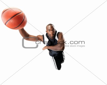 Young male basketball player jumping in air trying to dunk the b