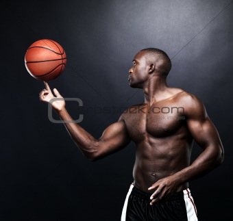 Fit afroamerica man spinning a basketball 