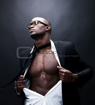 Fit for business - Man pulling his shirt open revealing well bui