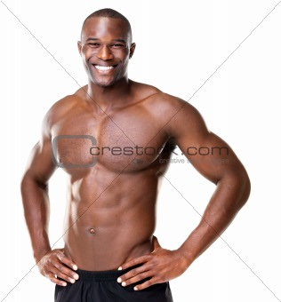 Happy bodybuilder with muscular physique posing against white