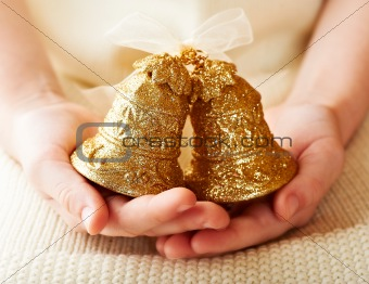 Child's hands holding beautiful christmas bells