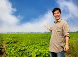 happy asian farmer showing his farm