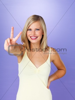 Woman smiling while giving peace sign