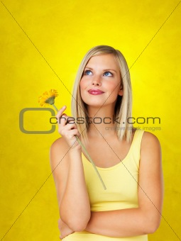Pretty woman holding flower while contemplating