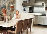 Open plan kitchen with female sitting at dining table in house