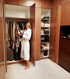Mature woman selecting clothes near wardrobe after a bath