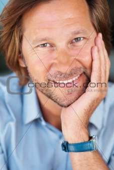 Happy relaxed mature man with hand on chin smiling