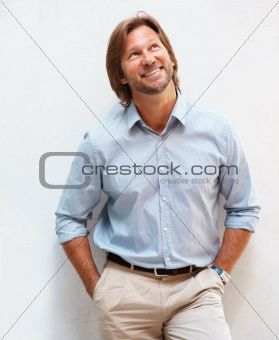 Happy smart man smiling over a happy thought , hands in pockets