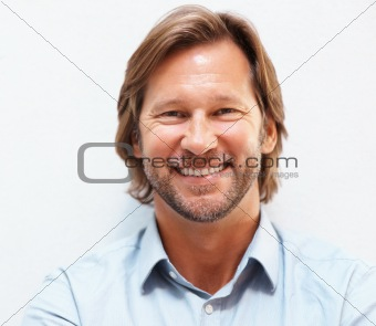 Closeup portrait of a happy mature man smiling against white