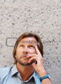 Mature man in a thoughtful pose looking up against wall