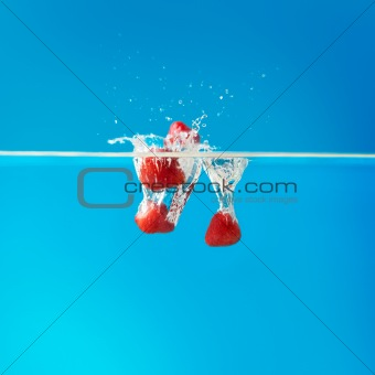 Strawberries splashing water