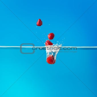 Strawberries dropped into water