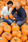 Couple picking pumpkin.