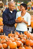 Couple buying pumpkin.