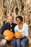 Couple holding pumpkins.