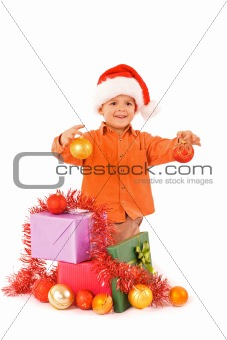 Boy in santa hat with christmas baubles and presents - isolated