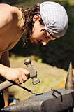 Young blacksmith hammering hot iron on anvil